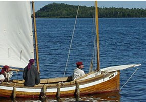 A wood sailboat - called a Mackinaw - approaches a dock at Grand Portage on Lake Superior.