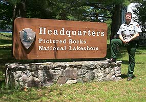 Park Ranger with Headquarters entrance sign