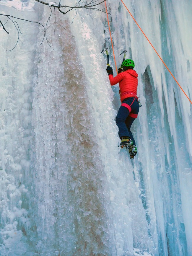 Ice climber ascending ice curtain