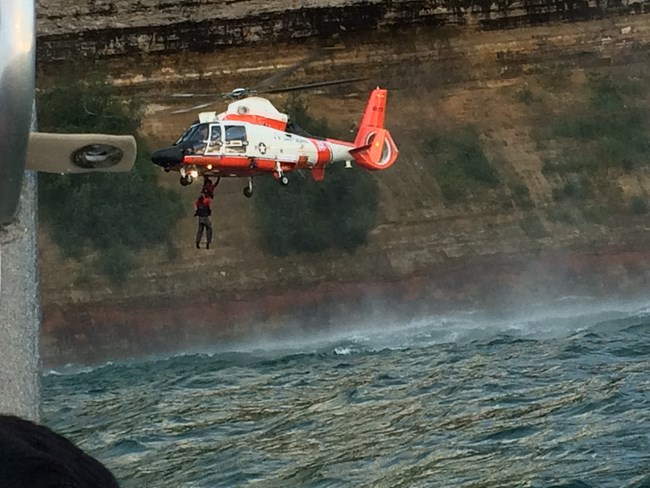 Coast Guard Helicopter hoisting kayaker from Lake Superior along cliffs in Pictured Rocks National Lakeshore
