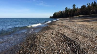 Small stones make up much of the shoreline on the beach at Lake Superior Overlook.