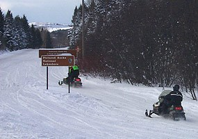 Two snowmobiles travel along County Road H-58 with the Grand Sable Dunes in the background.