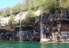Springtime waterfalls tumble over the Pictured Rocks cliffs into Lake Superior.