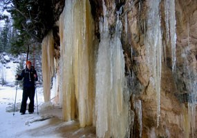 A winter camper took off his skis and posed next to large icicles created from seepage along the Pictured Rocks cliffs.