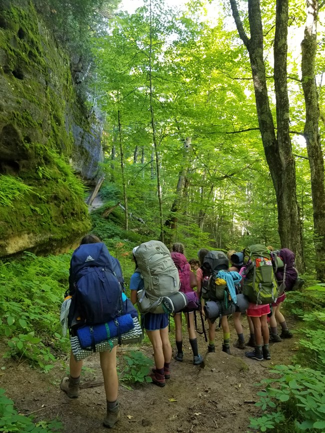 A group of backpackers on the North Country Trail standing on trail in forest