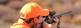 Person wearing hunter orange with rifle