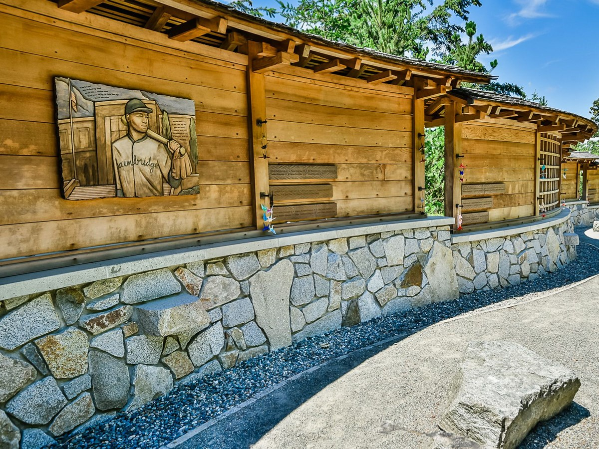 Curved wall constructed of cedar and stone with plaques in the upper portion.