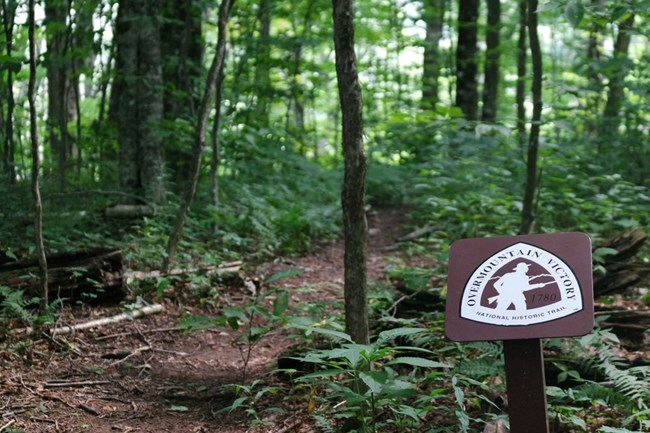 An Overmountain Victory National Historic Trail marker is to the right of a dirt path.