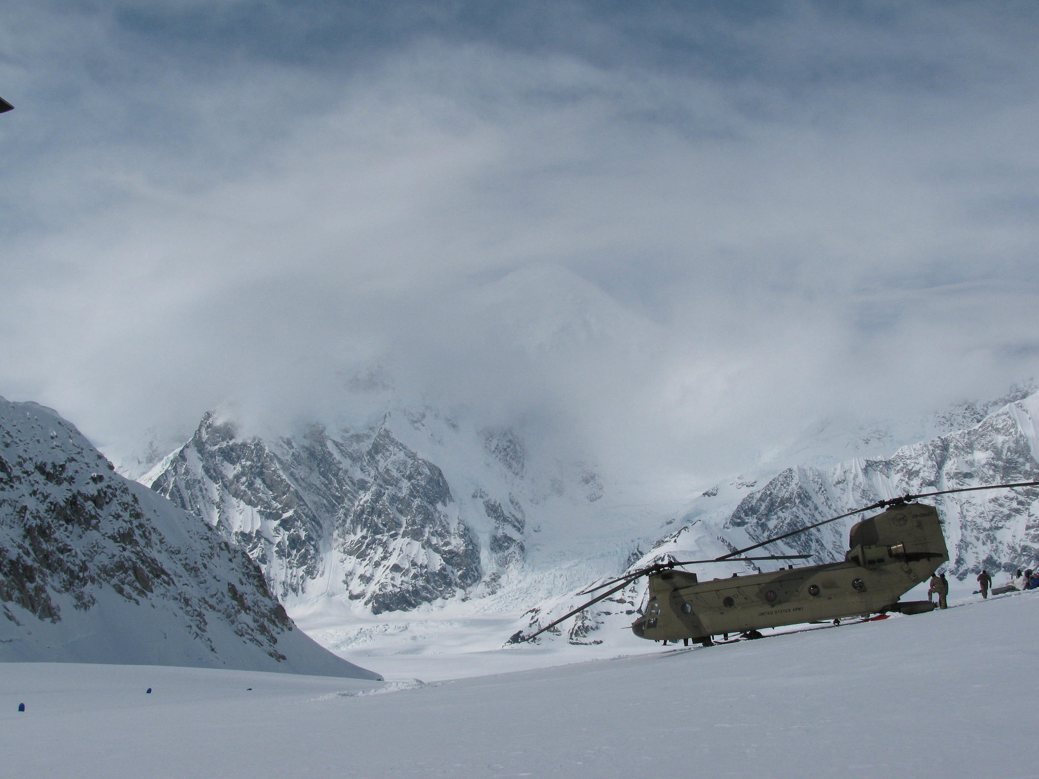 A CH-47 lands on the Kahiltna Glacier, surrounded by snowy peaks