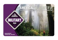 The 2021 America the Beautiful-The National Parks and Federal Recreational Lands Military Pass with a photo of a hiker looking skyward while standing in a forest of giant redwood trees.