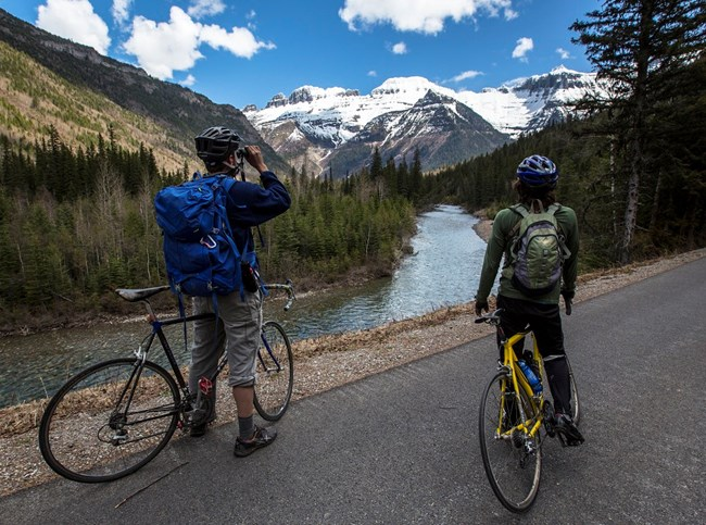 Two bicyclists stopped on a paved trail to enjoy the mountain scenery