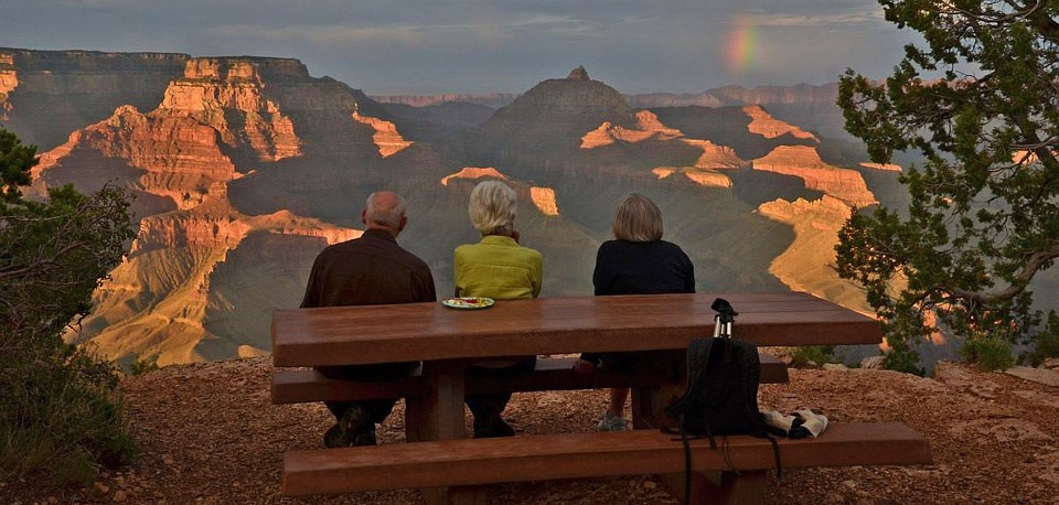 Three people sitting at a picnic table watching sunset and a rainbow over the Grand Canyon