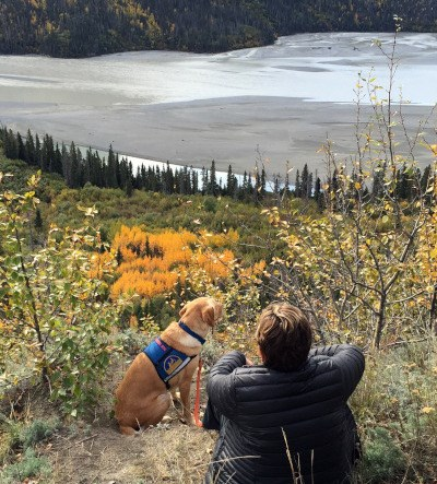 Woman and her service dog take in the view of Alaskan river and woods