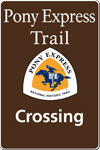 A brown tall rectangular highway sign with white text saying: Pony Express Trail Crossing and a triangular logo with orange and white and a blue pony rider.