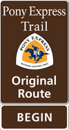 A brown tall rectangular highway sign with white text saying: Pony Express Trail Original Route BEGIN and a triangular logo with orange and white and a blue pony rider.