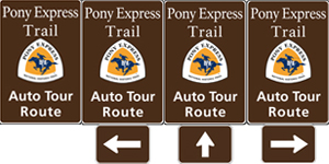 Four vertical rectangle brown highway signs with white text saying: California Trail Auto Tour Route and the triangular California Trail logo in yellow and white.