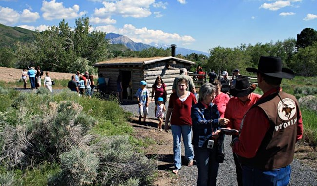 Many people gather around a grey wooden cabin surrounded by green shrubs and trees with mountains in the background.