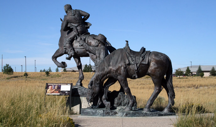 A single horse stands in front of a Pony Express rider on a horse in the form of a large bronze sculpture. An exhibit sits to the left.