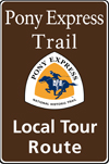 Brown tall rectanglular highway sign with white words: Pony Express Trail Local Tour Route and white, orange and blue trail logo of rider.
