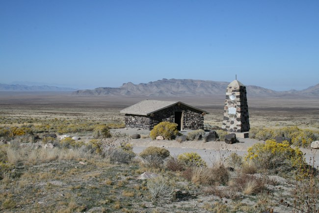 A stone cabin sits in a wide open, high desert plain.