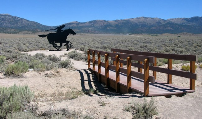 A bridge crosses over a dry drainage with sand and shrubs all around, and mountains in the background with a black steel silhouette of a rider and horse.