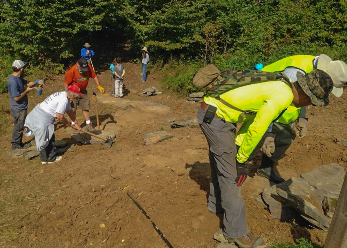 Volunteers work on installing stone steps on an earthen slope of the trail.