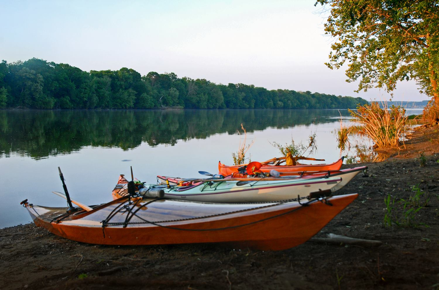 Kayaks resting on the shore of the Potomac River with the river and treeline in the background.
