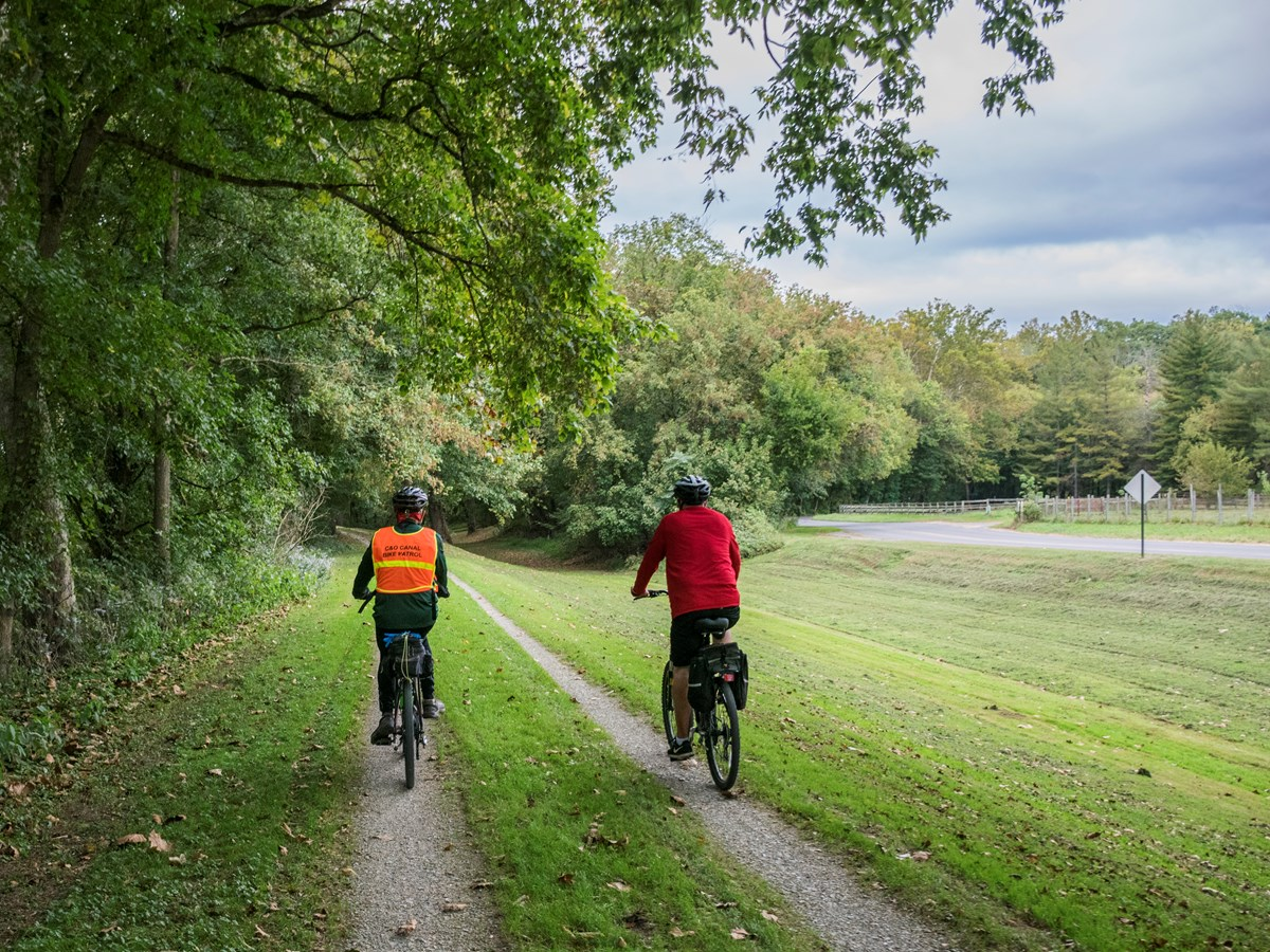 Two bikers travel along the grass and gravel towpath