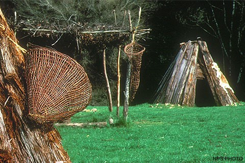 Part of a redwood kotca with a basket (left), a shade structure (center), and a second redwood kotca (right) at Kule Loklo.