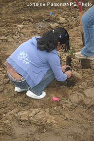 Young girl planting a buckeye tree.