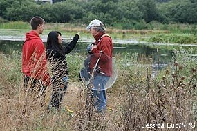 Volunteer Rick Johnson with two high school students listening to bird sounds in the Giacomini Wetlands.