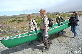 YCC crew members carrying a canoe to Abbotts Lagoon.