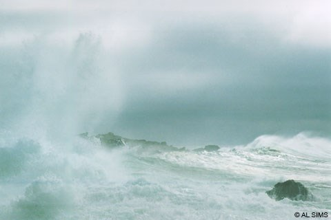Large white-capped ocean waves crashing on rocks during a storm.