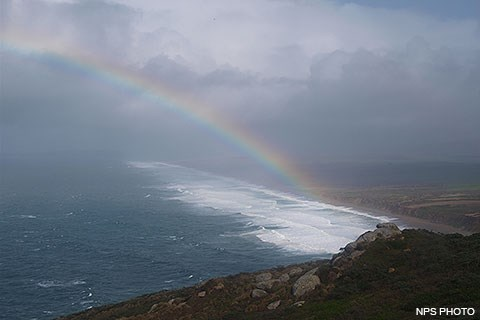 A rainbow arcs to the left above a stormy sea as big waves crash along a long straight beach on the right.