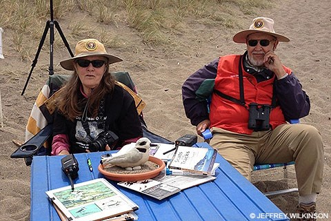 Two volunteers sitting a a blue-topped table with information about the western snowy plover.