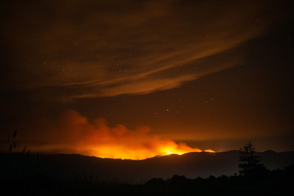Smoke rises above a ridge and reflects orange light generated by a wildfire burning on the ridge's far side. Stars are visible above the smoke.