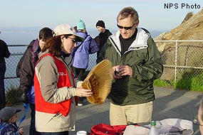 Docent with gray whale baleen talking with a visitor.