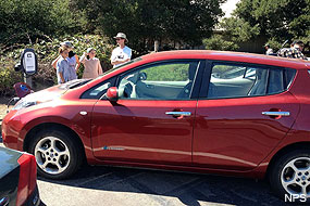 A family charging their electric vehicle at Bear Valley Visitor Center.