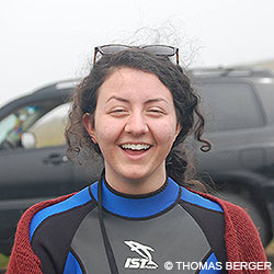 Point Reyes Social Media Team member Alyssa wearing a wetsuit and standing in front of a black vehicle.