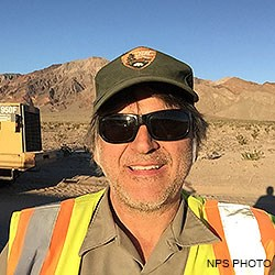 A head shot photo of Point Reyes Social Media Team member Jeff wearing an NPS ball cap, sunglasses, and a safety vest. The rear end of a large yellow wheel loader and desert mountains are in the background.