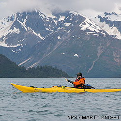 Kevin paddling a yellow kayak on Glacier Bay, with snow-capped peaks in the background.