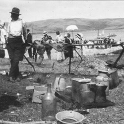 Black and white photo of people picnicking on a beach with water and hills in the background.