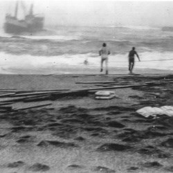 Black and white photo of two men on a beach with a ship surrounded by heavy surf very close to shore.