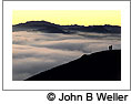 Fog-filled valley with yellow twilight glow over a ridge in the background. © John B. Weller. Click on this image to view the Soundslides presentation.