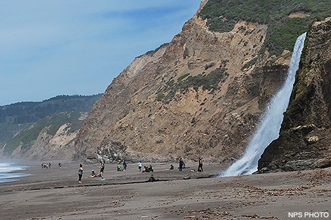 Twenty visitors playing and resting on an ocean beach. Pacific Ocean waves wash in from the left and a waterfall cascades onto the beach from a coastal bluff on the right.