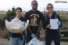 Three Beach Cleanup Volunteers with litter collected from Limantour Beach.