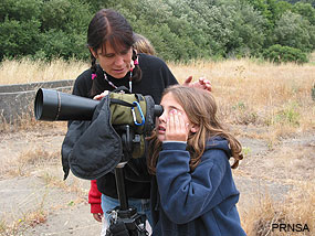 Woman helping young girl look at birds through spotting scope. PRNSA