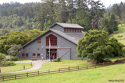 Visitors entering and exiting a gray barn-like visitor center surrounded by green pasture and trees.