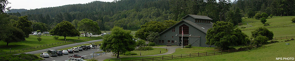 A gray barn-like visitor center surrounded by green fields and trees with a parking lot on the left.