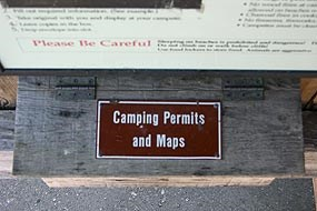 "Step 4. Below the ""Backcountry Camping Information After Hours Registration"" sign is a small wooden box labeled ""Camping Permits and Maps."""